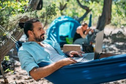 A man works on a laptop while lying in a hammock. A young handsome freelance guy lies in a hammock at a camping in the mountains among the trees and works remotely online on a laptop computer.