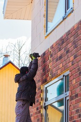 A man works with a drill, attaches thermal panels made of clinker to the facade of the house. Clinker bricks and tiles in brown color
