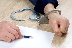 A man writes a confession at the police station. One hand is cuffed, the other is unbuttoned, pen in hand for writing explanations. Arrest, bail, felon, jail. the criminal's fingerprints