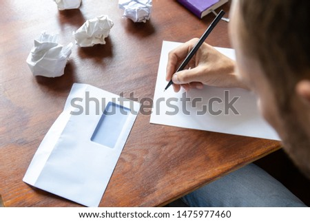 a man writes a letter on a sheet by hand