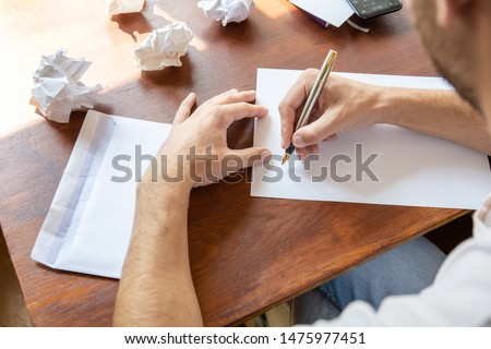 a man writes a letter on a sheet with a fountain pen