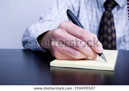 A man writing on a pad of paper.