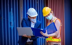 A Manager and dock worker under discussion about dock container shipping warehouse document,they wearing safety uniform hard hat and hold radio communication wearing face mask to protect virus.