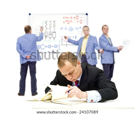 A manager, trying to understand some very complex theories, oblivious of the people in the background trying to explain it to him - stock photo