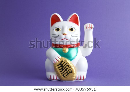a Maneki-neko plastic cat, Symbolizing luck and wealth, on a pop and colorful background.Minimal color still life photography