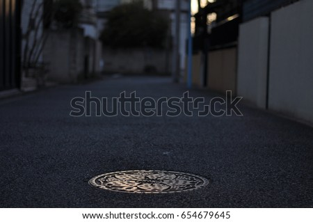 A manhole cover on the street and sunset in Tokyo residential area.