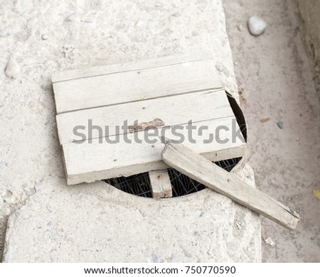 a manhole with a wooden cover #750770590