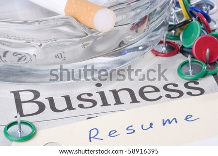 A manila resume folder laying on a business newspaper next to an ashtray with a filtered cigarette on it.