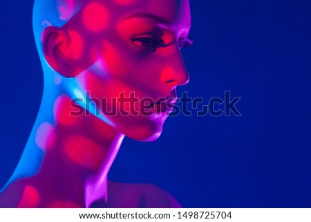 A mannequin on a blue background. The mannequin's face is partially illuminated by pink light. Girl model for shop window. Girl doll with make-up.
