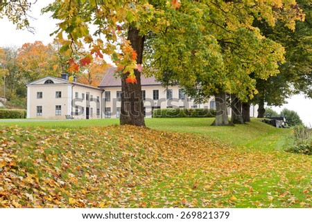 A manor, mansion and its garden, park in October.  Overcast but colorful garden with different plants of vegetation.