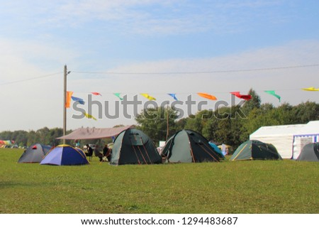 A many camp tents on the green grass near the forest on a blue sky background on summer day - beautiful nature landscape, sports tourism, camping, scouting, tourist life #1294483687