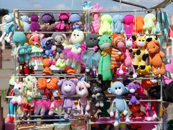 A many colored cute fluffy animals soft toys on display stand at outdoor fair at Sunny day