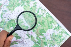 A map on a table. Detail topographic map. Man's hand holds a Magnifier, a Loupe. Terrain orientation. Trekking. Scouting Scout equipment for orientation in the forest. Orienteering Sports orientation