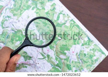 A map on a table. Detail topographic map. Man's hand holds a Magnifier, a Loupe. Terrain orientation. Trekking. Scouting Scout equipment for orientation in the forest. Orienteering Sports orientation #1472023652
