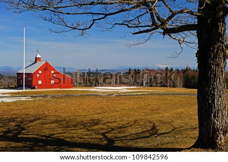 A Maple tree and flagpole frams a small red barn sits on the edge of a field partially covered with melting snow on a warm spring day in Vermont with a scenic view of the White Mtns in the distance.