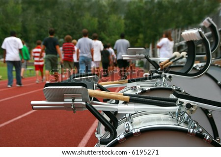 A marching band practices on the high school track before a parade