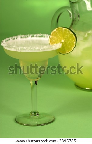 A margarita with a pitcher of margaritas behind it - stock photo