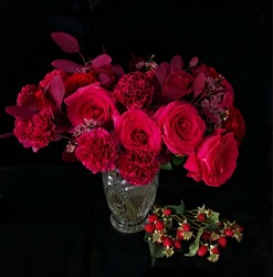 A maroon still life. Maroon roses and cloves in the crystal vase and crimson berries with the black background. Image with selective focus, noise effect and toning