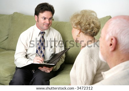 A marriage counselor or salesman listening to an elderly couple.   Could also be a salesman.