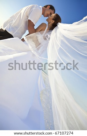 A married couple, bride and groom, about to kiss in sunshine on a beautiful tropical beach