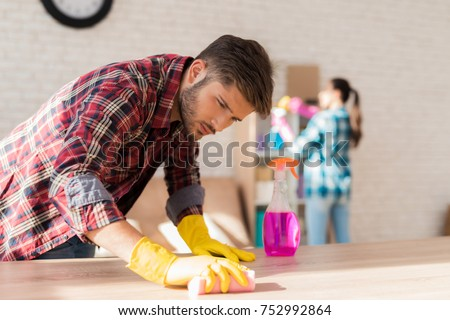 A married couple cleaning their apartment. They wipe the dust. They clean the furniture and the bookshelf from dirt. They work in rubber gloves, use sponges, water sprayers, dust brushes.