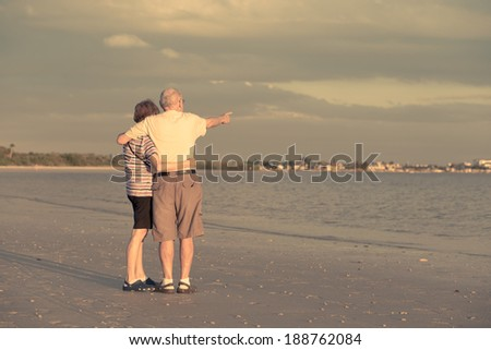A married couple in retirement on the beach at sunset in Florida pointing at something on the horizon.