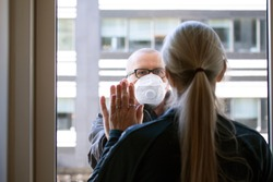A married couple separated by Corona Covid-19 virus. She is quarantined indoors and he is outside wearing protective mask. They are holding hands through a window glass looking lovingly at each other.