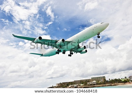 A marvelous side shot of a huge commercial airplane flying outside of a beach resort.