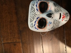 A mask of white with darkened eyes and teeth resembling a skull beautifully decorated on a wooden background.
