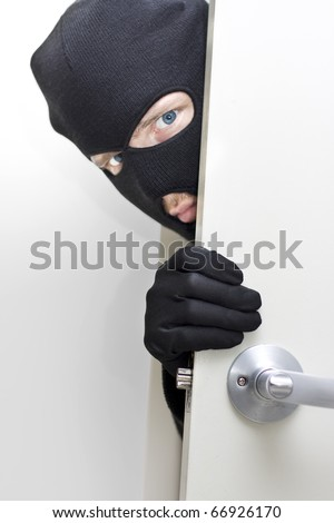 A Masked Intruder Peers Around The Corner While Breaking In A Properties Front Door