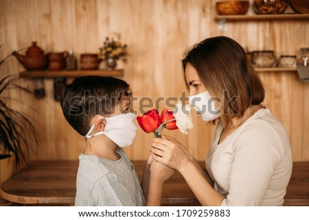 A masked son gives flowers to a masked mom. Mother's Day on self-isolation. Family quarantined.
