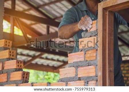 A mason builds brick wall in the house