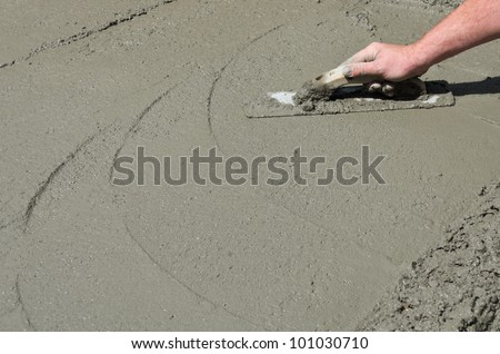 A mason hand finishes a newly poured concrete floor
