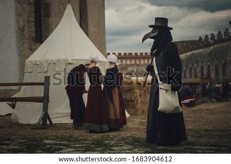 A masquerade historical scene reconstruction. Plague doctor in medieval old town. Castle and epidemic Stockfoto ©