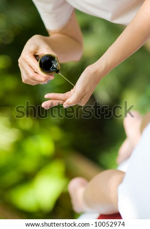 A massage therapist pours oil into her hands