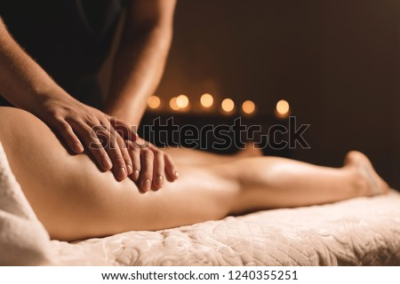 A masseur in a dark room does a hip massage with oil for a woman. Spa procedures massage women