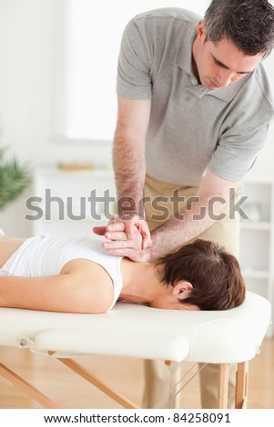 A masseur is massaging a female customer's neck in his surgery