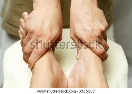 A masseuse massaging the feet of a woman - stock photo