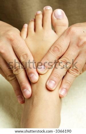 A masseuse massaging the foot of a woman