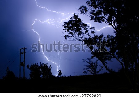 A massive branched lightning strike at night hitting the ground near high voltage power lines and silhouetted trees during a summer thunderstorm