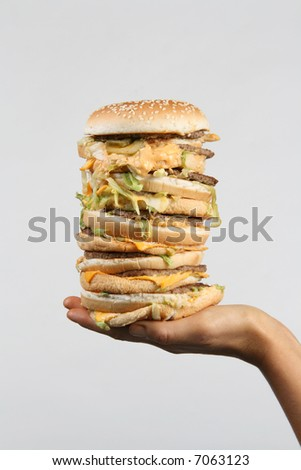 A massive burger held out on a hand