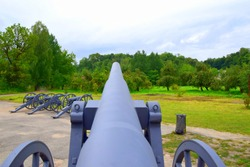 A massive cannon seen from the loading side with two wheels on the sides and three more cannons visible in the distance located on a path near a lawn and a set of trees seen during autumn day