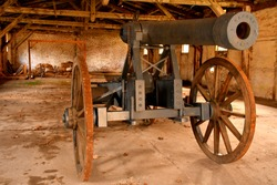 A massive metal artillery cannon with a brass grey frame on four wooden wheels used for historical reenactments standing inside an old abandoned barn, shack, or barracks full of debris and wooden roof