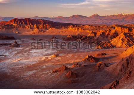 Photo of  A massive moon crater with salt deposit in the middle of eerie terrain at the Valle de Luna, or Moon Valley, at San Pedro de Atacama. Sunset light casts shadow on mountains and changes its colours.