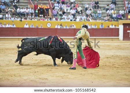 A matador fighting in a typical Spanish bullfight.