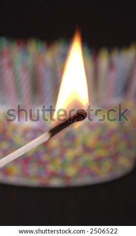 A match preparing to light a cake with a myriad of candles. Shallow depth of field.