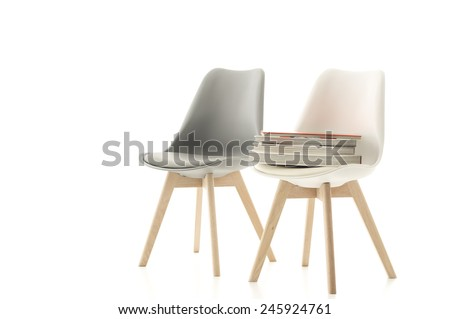 A matching stylish grey and white modern molded chair with wooden legs standing side by side with a pile of books on one seat over a white background with copyspace #245924761