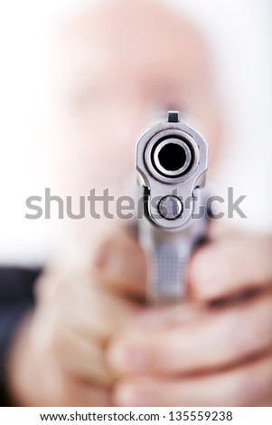 A mature adult man wearing a suit, holding a 9mm gun with both hands aiming it to the camera. Isolated on white background.