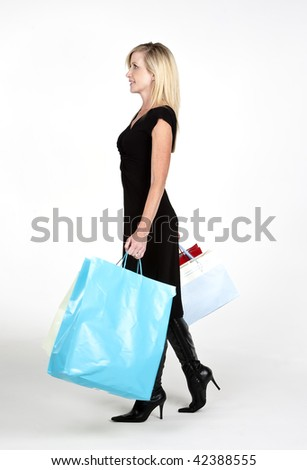 A mature attractive woman shopping with bags in hand.