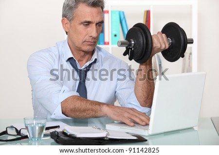 A mature businessman lifting weights in his office.